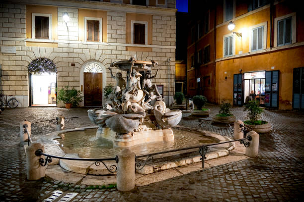 A night view of Piazza Mattei in the heart of the Jewish Ghetto of Rome Rome, Italy, January 07 -- A beautiful night view of Piazza Mattei in the heart of the Jewish Ghetto of Rome, with the famous Fontana delle Tartarughe, a Renaissance fountain with bronze figures of young people, turtles and dolphins, attributed to the architect Giacomo della Porta and built in 1581. Image in HD format. ancient rome stock pictures, royalty-free photos & images