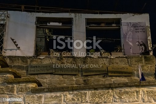 istock Night view of religious signs hanging on the wall of an abandoned building in the old part of Nazareth in Israel 1198255933
