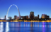 The city of St. Louis, Missouri, as seen from across the river.  The Gateway Arch dominates the left upper section of the photo, more than twice as high as any of the buildings in the photo.  In a horizontal line across the background and behind the Gateway Arch are downtown buildings and some skyscrapers.  Lights are just coming on in the buildings even though there is still light in the sky.  A line of beach lies between the buildings and the river, which is a dark blue, mirroring the dark blue of the sky.
