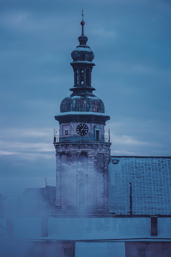 Aerial view of the Bernardine church and monastery in L'viv, Ukraine. Snowy roofs and a bell tower with a cross and a clock on a twilight winter sky. Dramatic cityscape in the smoke from the chimney