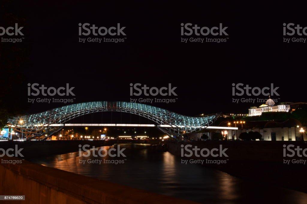Night view of The Bridge of Peace (Georgian: mshvidobis khidi) is a bow-shaped pedestrian bridge, a steel and glass construction illuminated with numerous LEDs, over the Kura River in Tbilisi, Georgia stock photo