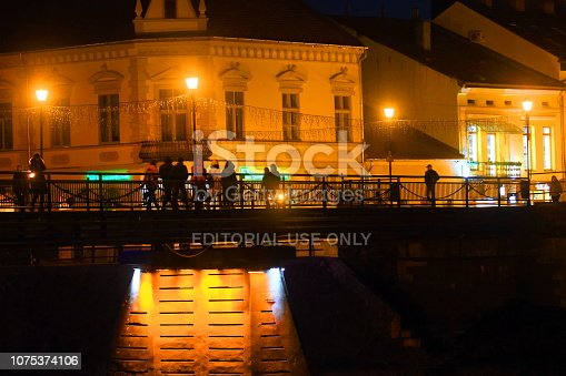 istock UZHGROROD UKRAINE - NOVEMBER 17, 2018: Night view of the bridge with pedestrians in the old part of the city. 1075374106