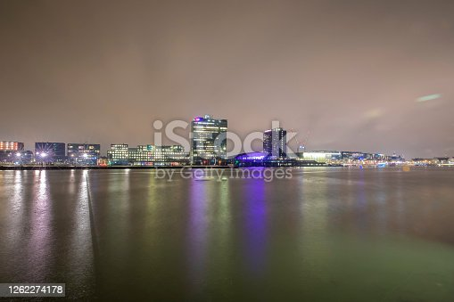 Night view over the Ij river with reflection of modern buildings in water in Amsterdam, the Netherlands