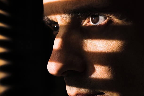 Night watcher Close up of a male face illuminated through a window blind. Focus on the eye. ambush stock pictures, royalty-free photos & images