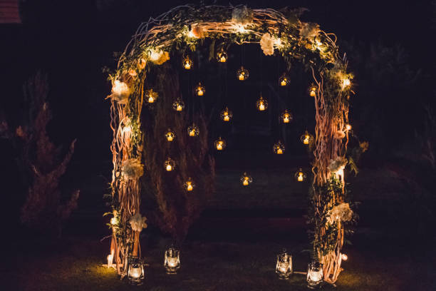 Night wedding ceremony, arch on party decorated with lights and candles in round glass spheres Night wedding ceremony, arch on party decorated with lights and candles in round glass spheres natural arch stock pictures, royalty-free photos & images