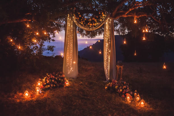 Night wedding ceremony with a lot of lights, candles, lanterns. Beautiful romantic shining decorations in twilight Night wedding ceremony with a lot of lights, candles, lanterns. Beautiful romantic shining decorations in twilight natural arch stock pictures, royalty-free photos & images