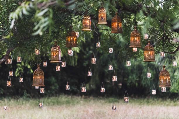 nacht-hochzeits-zeremonie mit viel vintage lampen und kerzen am baum - grüne wald hochzeiten stock-fotos und bilder