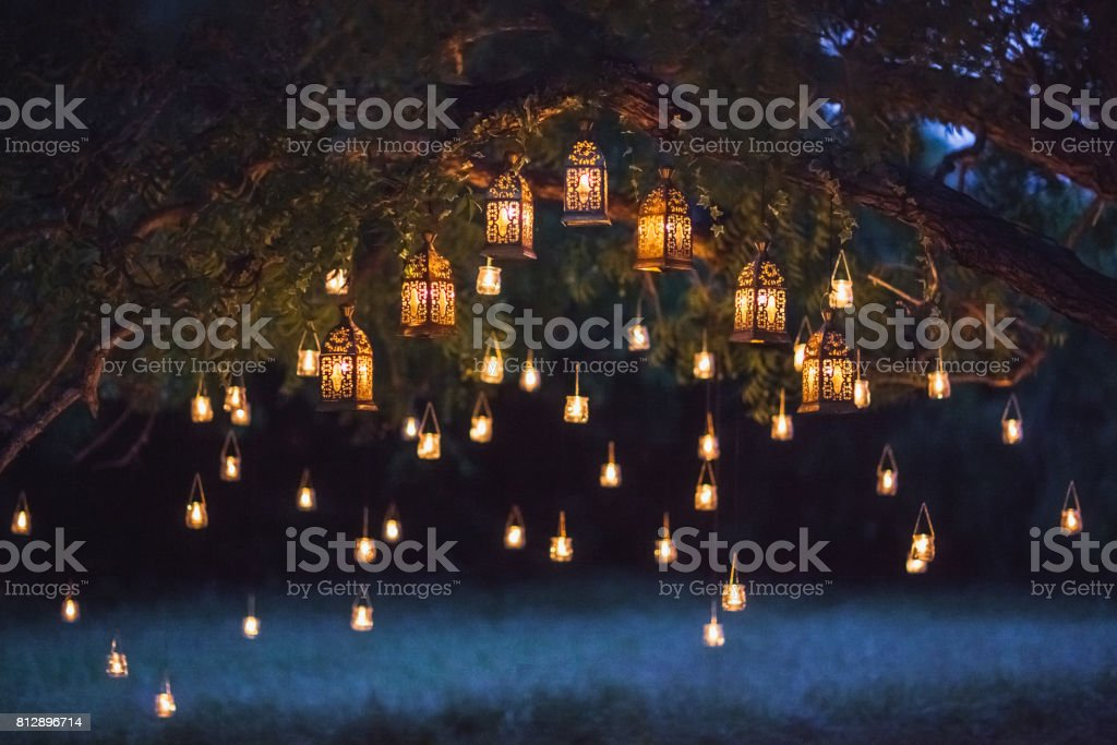 Night wedding ceremony with a lot of vintage lamps and candles on big tree royalty-free stock photo
