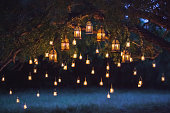 Night wedding ceremony with a lot of vintage lamps and candles on big tree