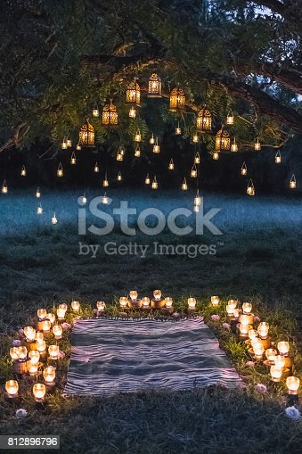 istock Night wedding ceremony with a lot of vintage lamps and candles on big tree 812896796