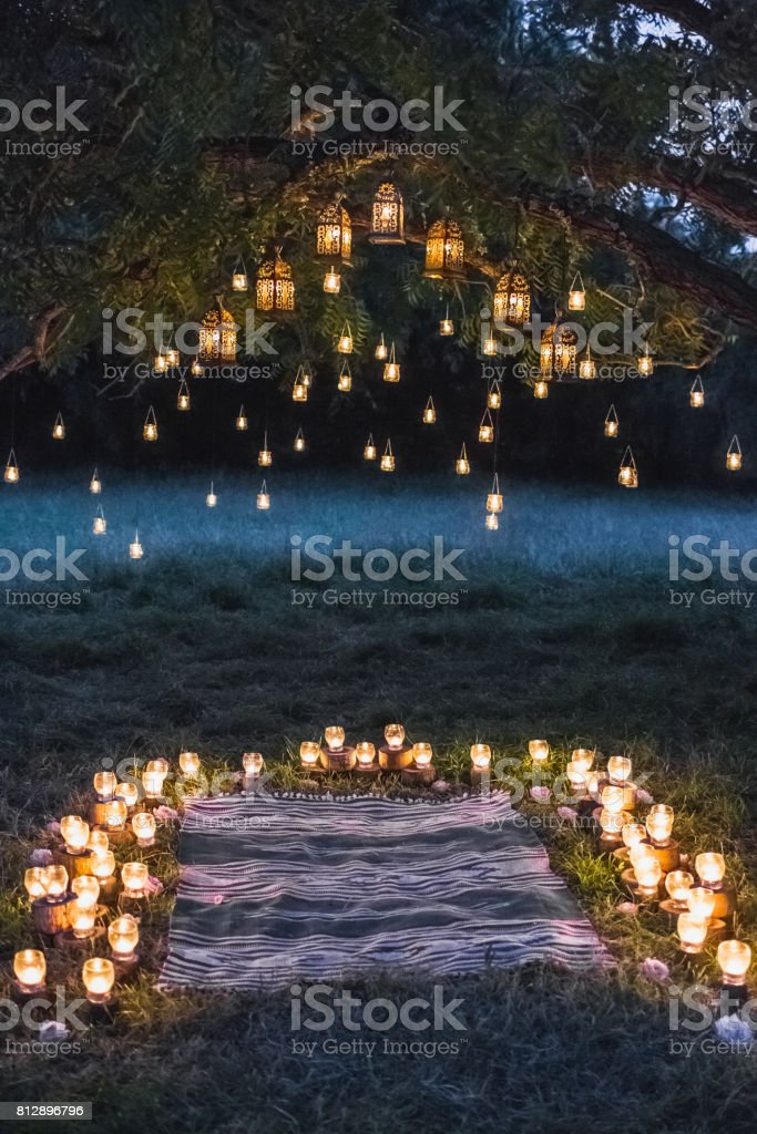 Night wedding ceremony with a lot of vintage lamps and candles on big tree stock photo
