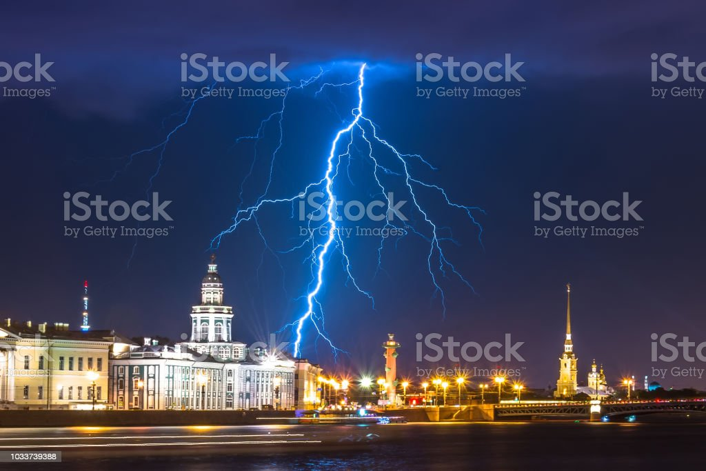 Night with lightning thunderstorm flash over the Neva in Saint-Petersburg and the Kunstkamera, Peter and Paul Fortress and Rostral column. stock photo