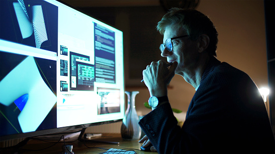 Close up stock photograph of a mature man working with a large computer screen. He's working with 3D software examining complicated shapes.