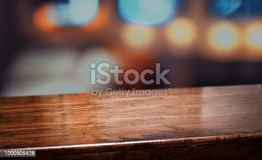 1044304084 istock photo nightclub background.Empty diagonal brown wooden table with blur bar restaurant bokeh lights,banner mockup template for display of product 1200905428