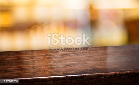 1044304084 istock photo nightclub background.Empty diagonal brown wooden table with blur bar restaurant bokeh lights,banner mockup template for display of product 1217267034