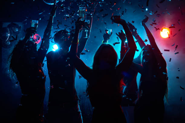Nightclub party with confetti Silhouette of young people with raised flutes having fun and clubbing entertainment club stock pictures, royalty-free photos & images