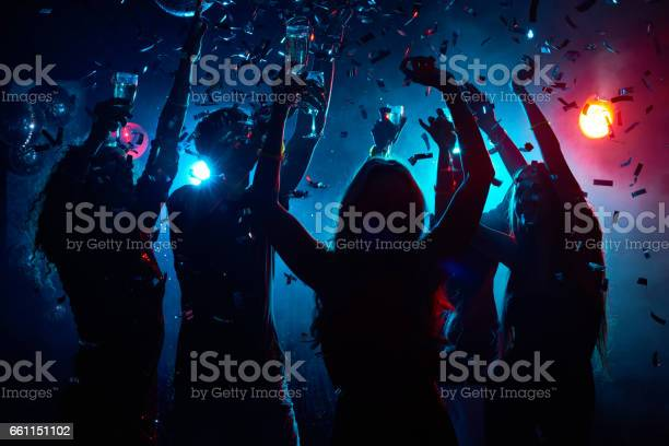 Silhouette of young people with raised flutes having fun and clubbing