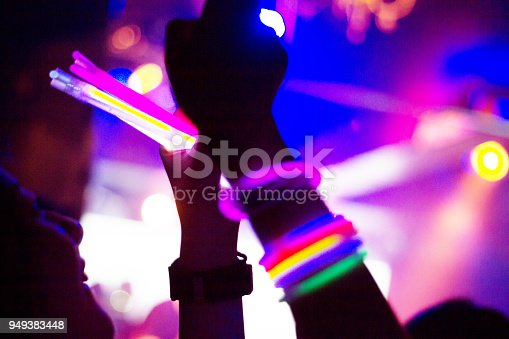 Side view of people enjoying music concert at a nightclub. They are having fun with taking picture with mobile phone.