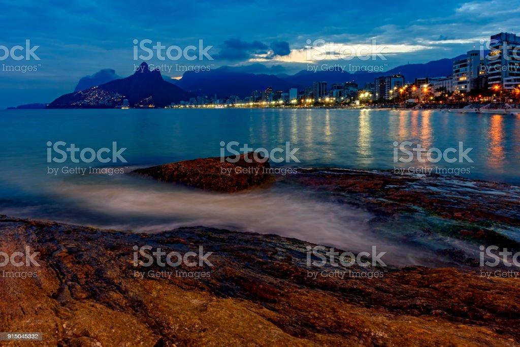 Nightfall at Ipanema beach and Arpoador stone stock photo