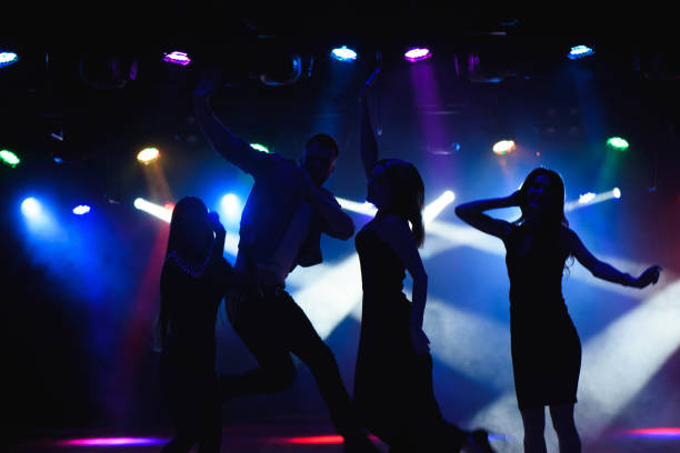 Nightlife and disco concept. Young people are dancing in club. stock photo