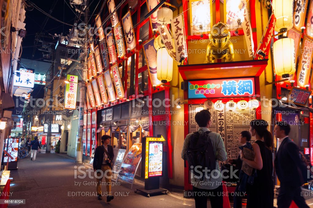 Nightlife on street of Osaka City along with shops, bars, and restaurants decorated with neon signs at night stock photo