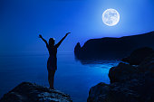 Woman stand with hand up to moon.