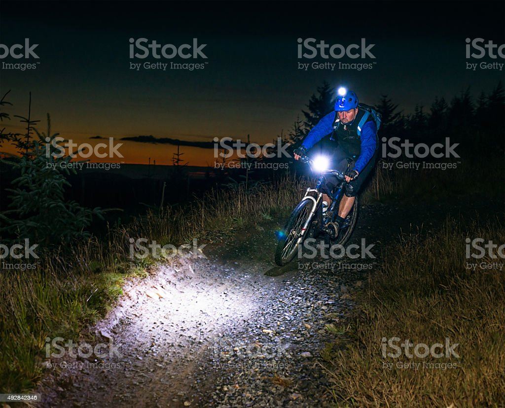 Night-ride mountiain biking with lights stock photo