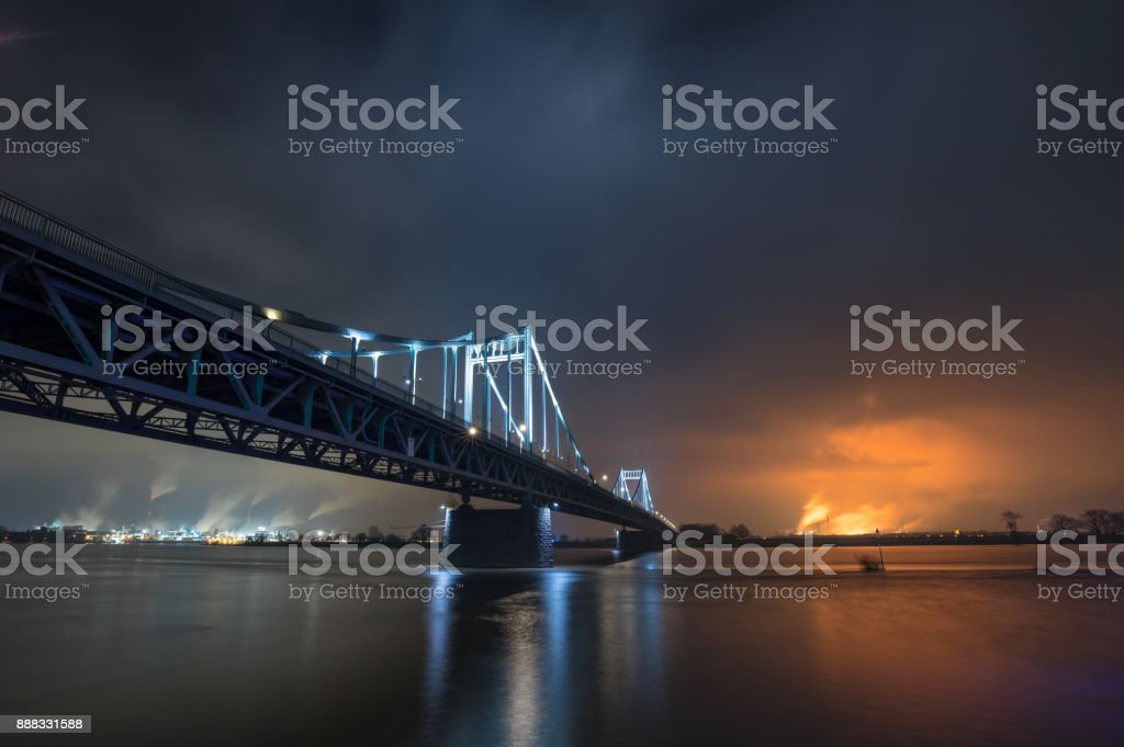 Nightshot Of Illuminated Historical Iron Bridge across the River Rhine at Krefeld Uerdingen View To Duisburg stock photo