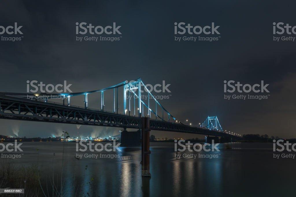 Nightshot Of Spotlighted Historical Iron Bridge across the River Rhine at Krefeld Uerdingen View To Duisburg stock photo