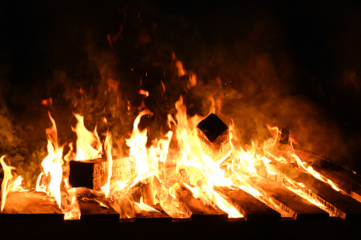 Roaring flames from wood on fire outdoor at night.