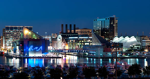 A nighttime picture of Baltimore, Maryland A view of Baltimore, Maryland's cityscape overlooking the Inner Harbor and Patapsco River at night. inner harbor baltimore stock pictures, royalty-free photos & images