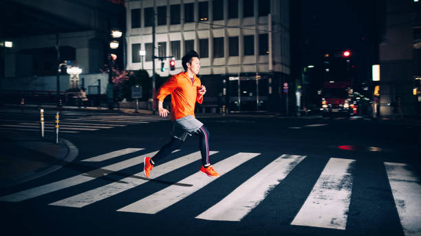 course de nuit à tokyo japon - passage balisé photos et images de collection