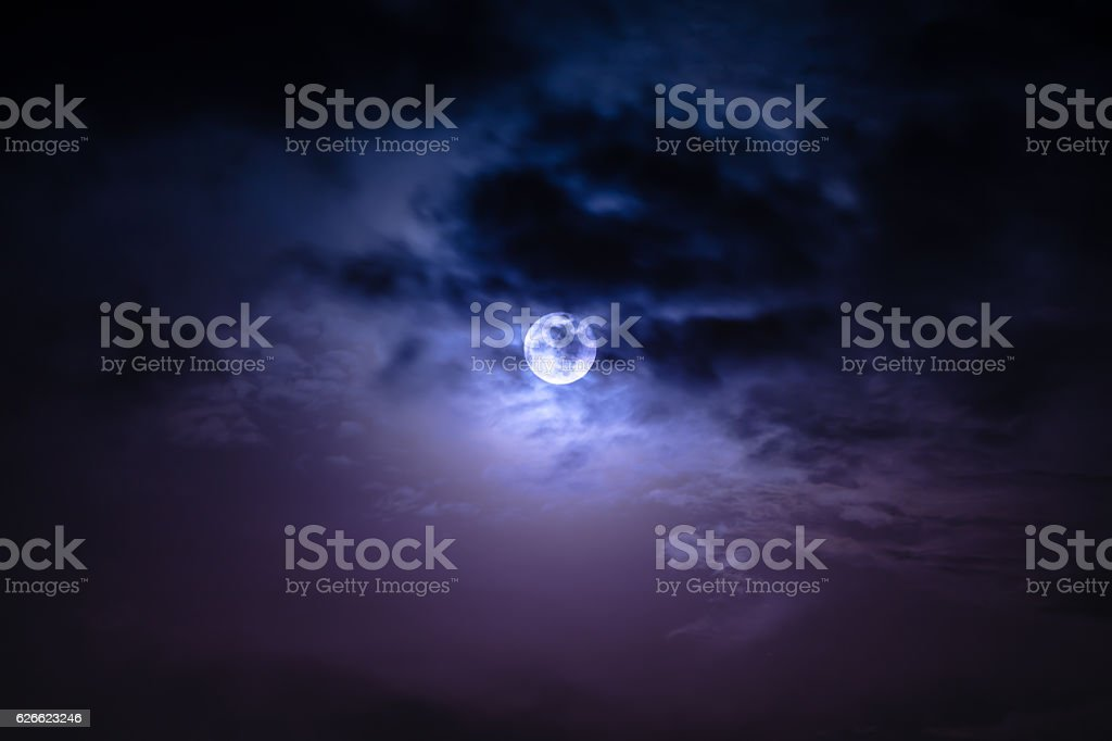Nighttime sky with clouds and bright full moon with shiny. stock photo