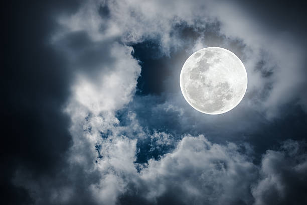 Nighttime sky with cloudy and bright full moon. Outdoors. stock photo
