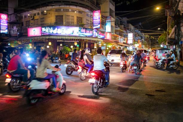 nighttime street scene in phnom penh, cambodia - motorbike, umbrella stock photos and pictures