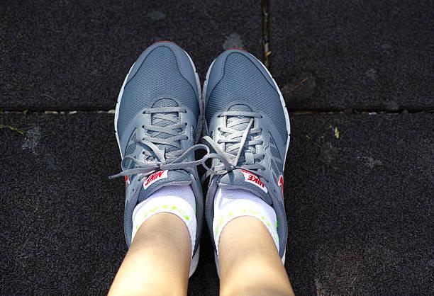 nike downshifter laufschuh auf frau füße - nike damen sneaker stock-fotos und bilder