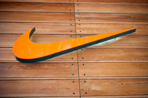 London, United Kingdom - April 22, 2011: Nike store logo located in central London, near Covent Garden. The Nike Swoosh logo hanging from a house wall. Nike is a global sports clothes and running shoes retailer. Nike stores are located all over London. Covent Garden is a famous shopping area and tourist hot-spot.
