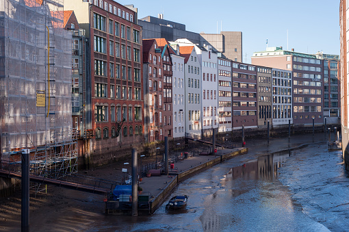 Nikolaifleet at low tide and view on historic buildings in Deichstrasse in Hamburg, Germany.