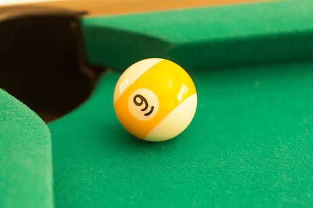 Nine ball at the edge of the pocket stock photo