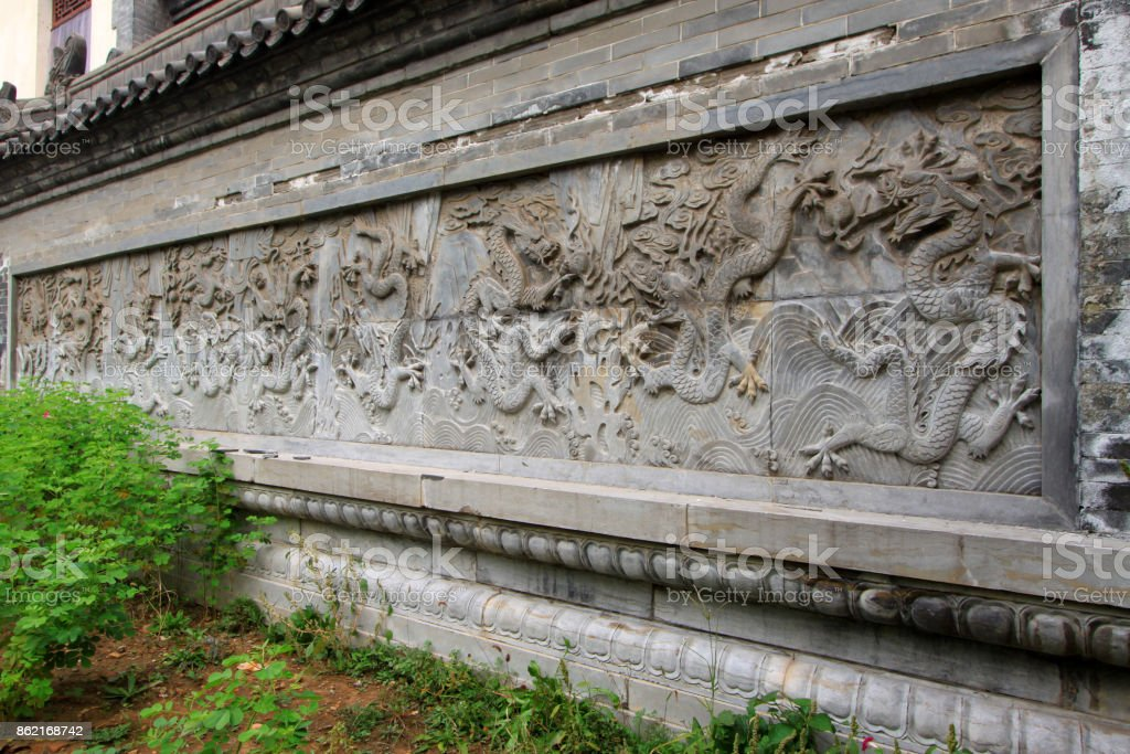 nine dragon wall in a temple, Chinese ancient architecture landscape stock photo