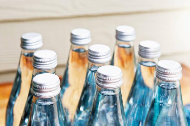 Nine glass screw-top bottles of bottled water stock photo