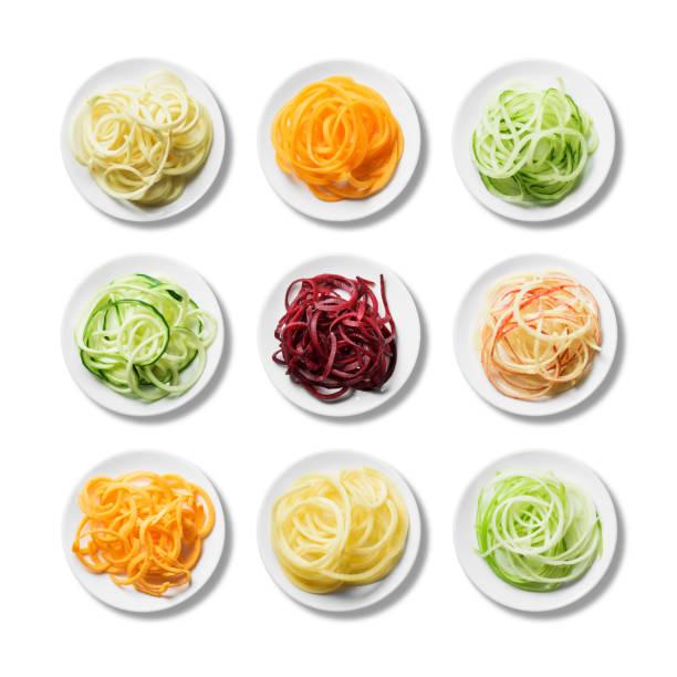 Nine plates of fresh, bright spiralised fruit and vegetables stock photo
