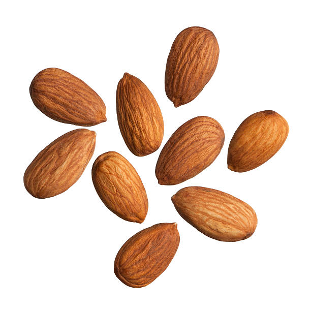Nine scattered almonds on a white background stock photo