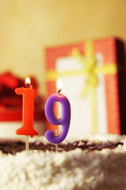 nineteen years. birthday cake with burning candles and gifts - number 19 stock photos and pictures