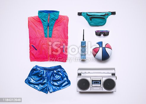 Fluorescent windbreaker style clothing from the 1990's, along with accessories: fanny pack, brick phone, boombox, sunglasses, and basketball.  Knolling layout.