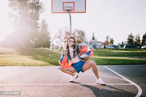A young woman plays on a basketball court wearing a fluorescent windbreaker style, from the 1990's, along with accessories: fanny pack, brick phone, boombox, sunglasses, and basketball.