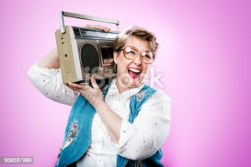 A portrait of a  woman wearing clothing and accessories from the 1990's, a bright pink colored background behind her.  She holds a personal stereo system on her shoulder.