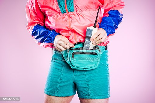 A man wearing fluorescent colored clothing puts a 1980's - 1990's cellular brick phone into his fanny pack, representing state of the art style and technology for that time.  Detail shot; horizontal with pink background.
