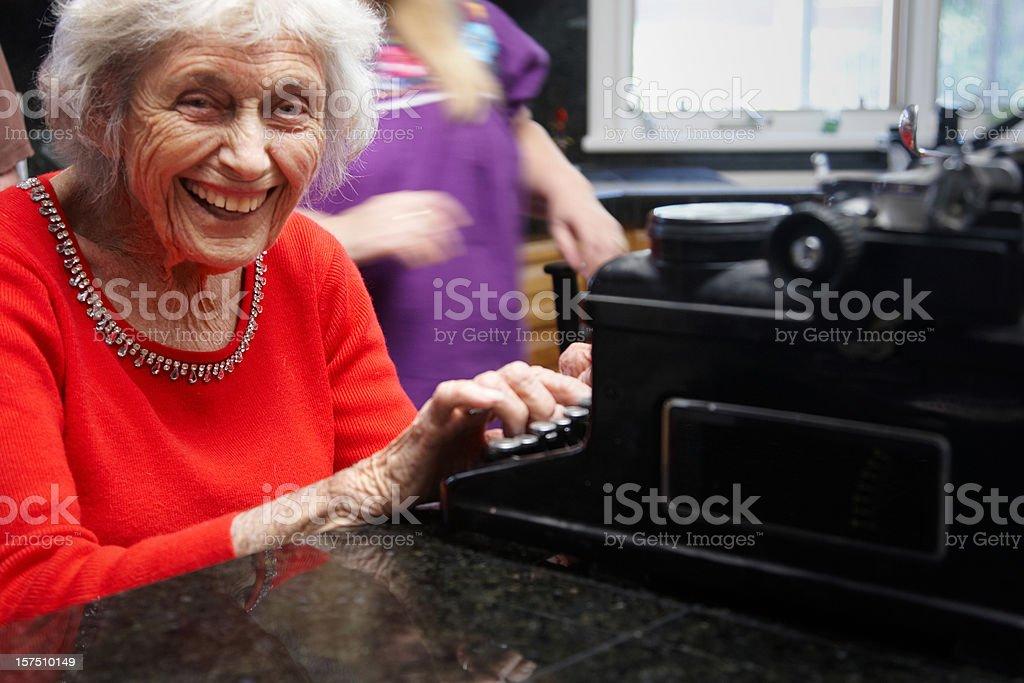 Ninety year lady on old typewriter royalty-free stock photo