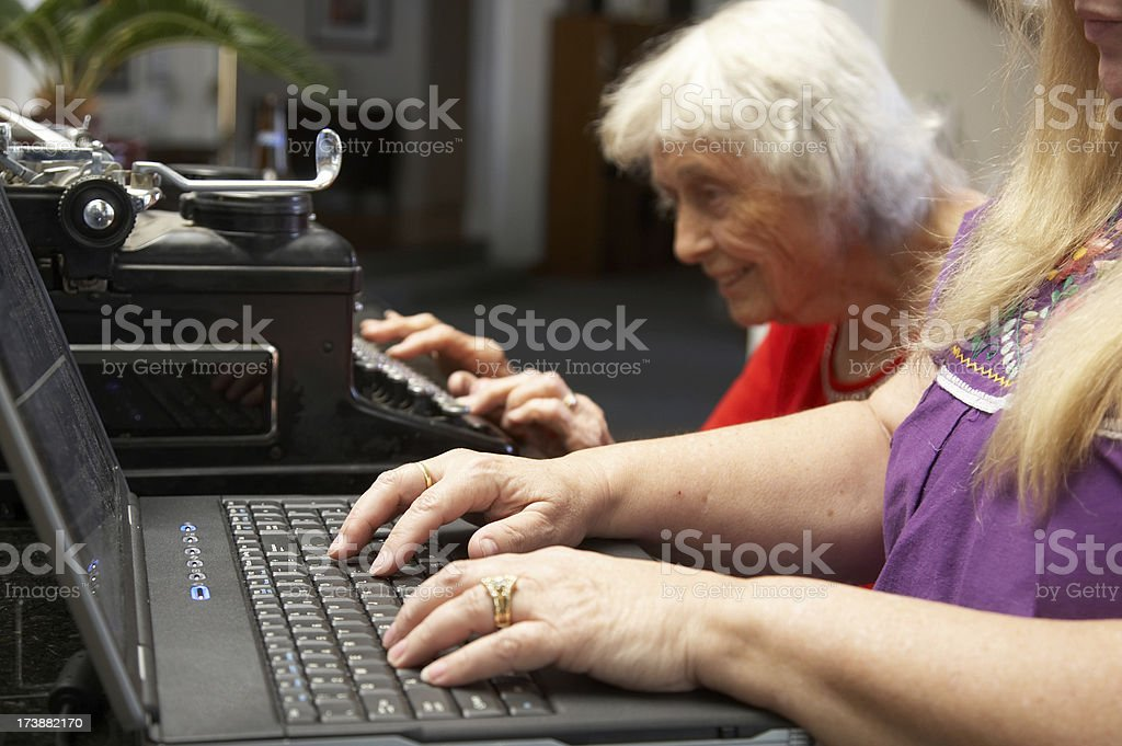 Ninety year old lady on typewriter younger woman laptop royalty-free stock photo